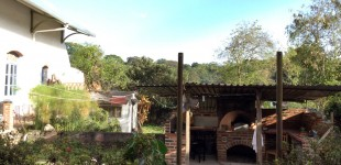 This wood fired pizza oven has a vocanic rock floor and door, a digital thermometer, and a clay roof built by Elsa Naveda